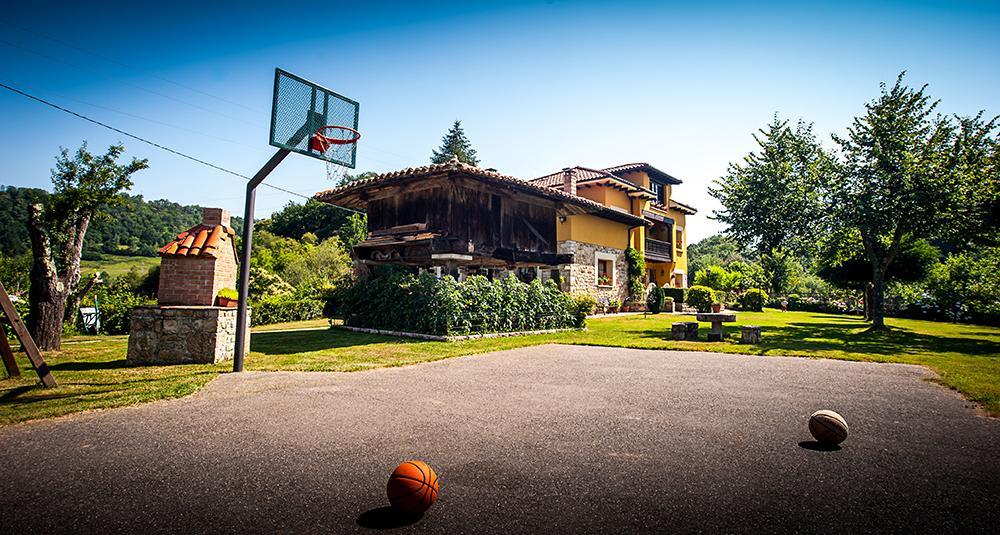 Cancha de Baloncesto y jardín con el hórreo y la casa al fondo